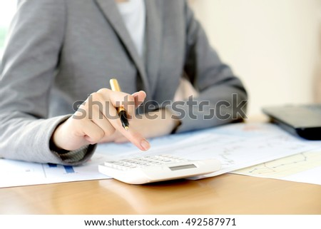 Businesswoman Analyzing Report On Chart With Calculator