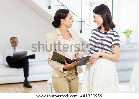 Businesswoman and a colleague interacting and holding diary in the office - stock photo
