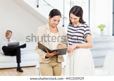 Businesswoman and a colleague looking at diary in the office - stock photo
