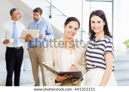 Businesswoman and a colleague smiling at camera while businessmen discussing in the background - stock photo