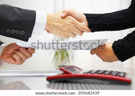 businesswoman and businessman are handshaking and exchanging contract documents - stock photo