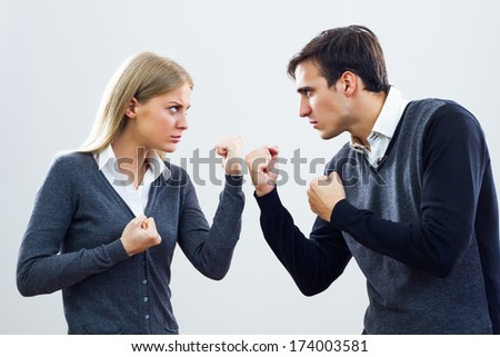 Businesswoman and businessman are very angry at each other and they are fighting,Rivalry at work - stock photo