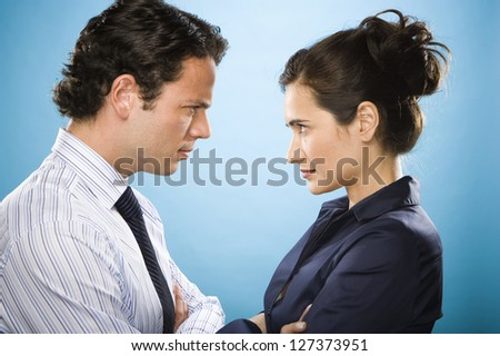 Businesswoman and businessman facing each other with pretended anger - stock photo