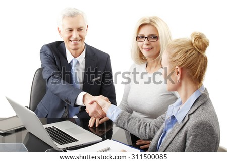 Businesswoman and businessman shaking hands while sitting at desk in front of laptop. Executive sales woman sitting in background. Business team making a deal. Isolated on white background.  - stock photo