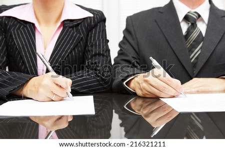 businesswoman and businessman signing contract after negotiations - stock photo
