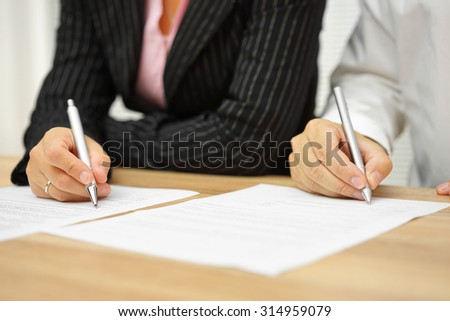 businesswoman and businessman signing contract in the office - stock photo