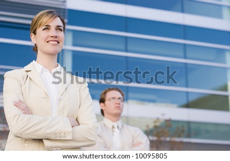 businesswoman and businessman standing side by side with arms folded looking forward - stock photo