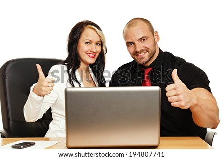 Businesswoman and businessman with thumbs up in front of a notebook computer.