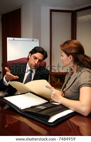 Businesswoman and businessman working on documents in an office - stock photo