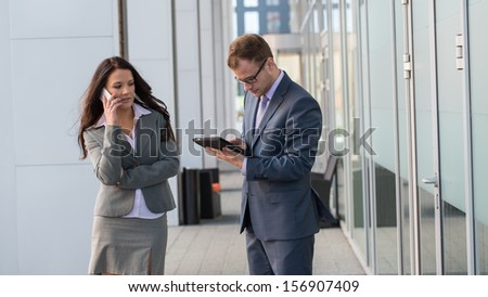 Businesswoman and businessman working outside with mobile phone and tablet pc. - stock photo