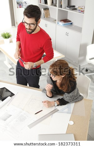 Businesswoman and businessman working together in small architect studio.