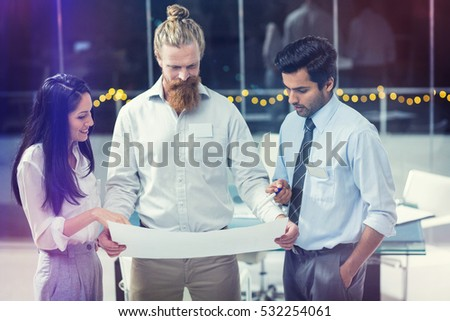 Businesswoman and businessmen discussing over blueprint in office