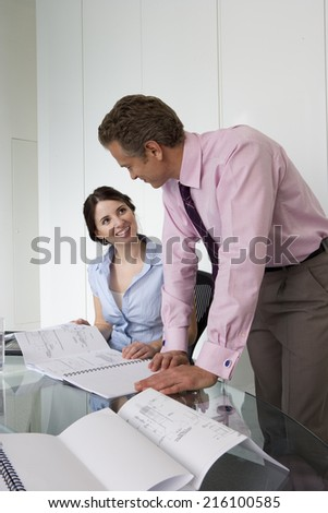 Businesswoman and colleague with paperwork