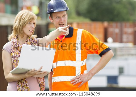 Businesswoman and construction worker with laptop discussing new project or working plan - stock photo
