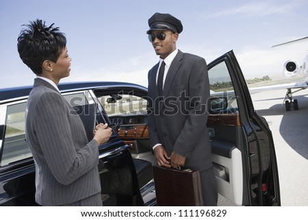 Businesswoman and driver standing by car on airfield - stock photo