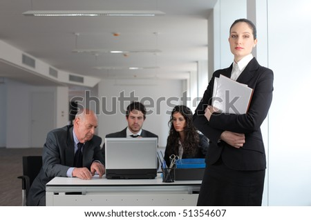 Businesswoman and group of business people at a desk on the background - stock photo