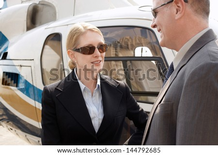 Businesswoman and man in discussion by helicopter - stock photo