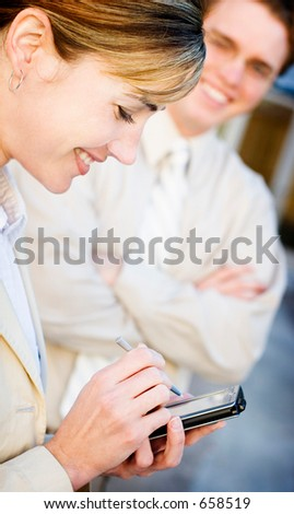 Businesswoman and man smile while working on project - stock photo