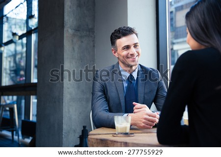 Businesswoman and smiling businessman discussing in restaurant - stock photo