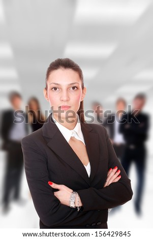Businesswoman arms crossed in front of her Business team in the office - stock photo
