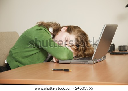 Businesswoman asleep at her desk. - stock photo