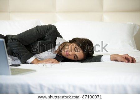 Businesswoman asleep on the bed, hotel or domestic room - stock photo