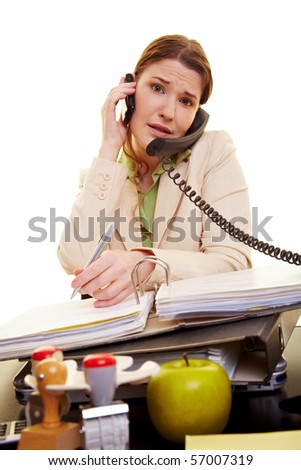 Businesswoman at her desk on the phone taking notes - stock photo