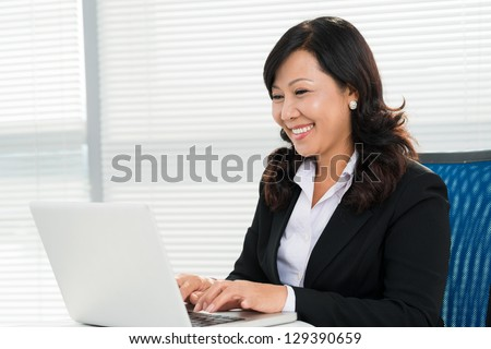 Businesswoman at her workplace at office - stock photo