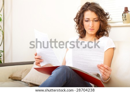 businesswoman at home doing paperwork - stock photo