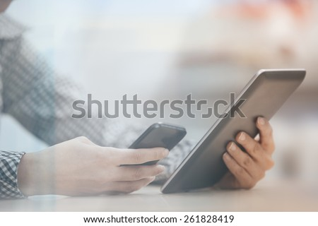 Businesswoman at office working with digital tablet and smartphone beinhd the window - stock photo