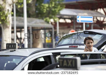 Businesswoman at Taxi on Cell Phone - stock photo