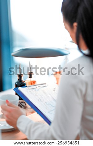 Businesswoman at work. Rear view of beautiful young woman in formalwear looking at clipboard with analytics while sitting at the restaurant - stock photo