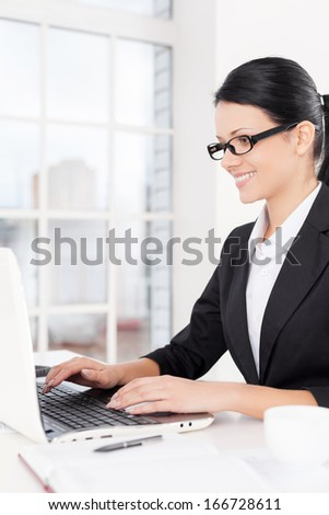 Businesswoman at work. Side view of confident young business woman using computer and smiling while sitting at her working place