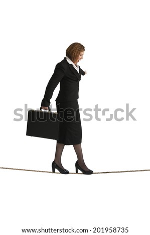 businesswoman balancing on a tightrope isolated on a white background - stock photo