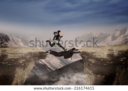 Businesswoman belief on her partner to help she through the cliff - stock photo