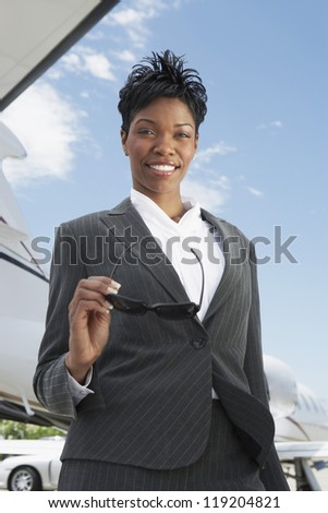 Businesswoman Beside an Airplane - stock photo