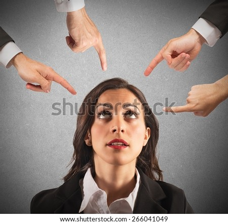 Businesswoman blamed unfairly by her work colleagues - stock photo