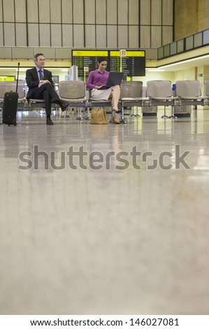 Businesswoman by businessman using laptop in the airport lobby - stock photo
