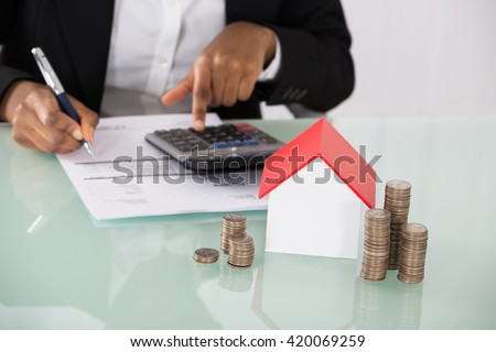 Businesswoman Calculating Invoice With House Model And Stack Of Coins On Desk - stock photo