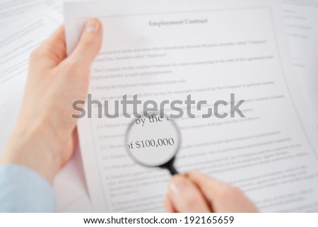 Businesswoman carefully analyzing the financial terms of a contract or another document with a magnifying glass. - stock photo