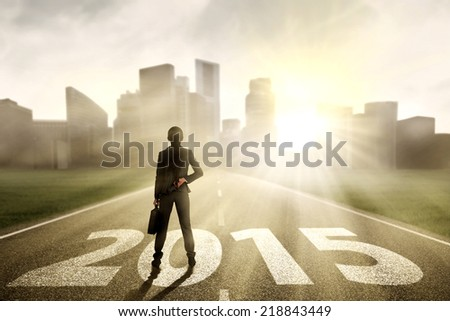 Businesswoman carrying briefcase, standing on the road and looking future 2015