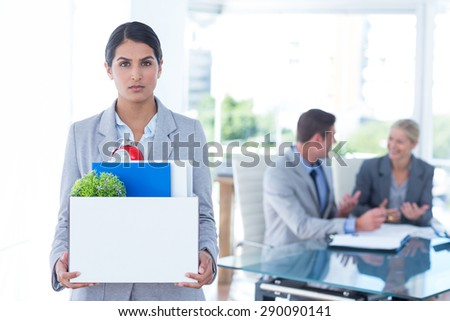 Businesswoman carrying her belongings in box after being fired - stock photo