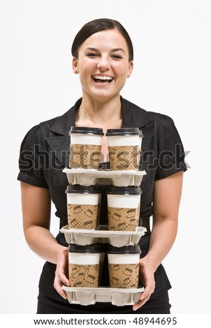 Businesswoman carrying stack of coffee cups - stock photo