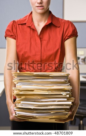 Businesswoman carrying stack of file folders - stock photo