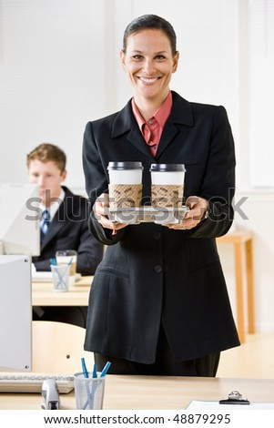Businesswoman carrying tray of coffee - stock photo