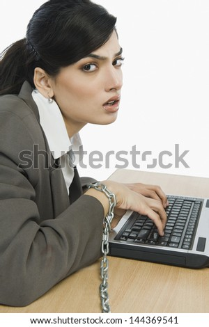 Businesswoman chained to her desk - stock photo
