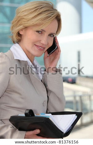 Businesswoman checking her diary smiling - stock photo