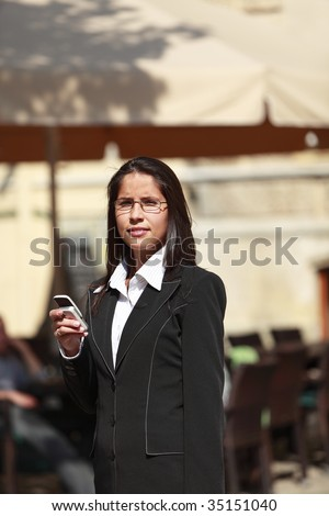 Businesswoman checking her mobile phone in a city. - stock photo