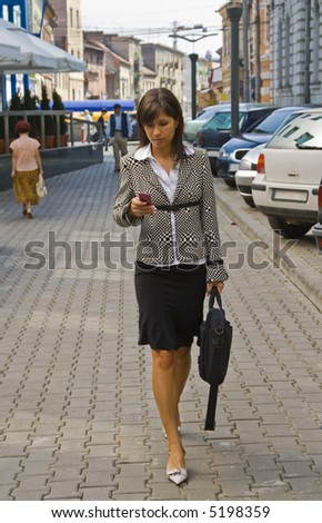 Businesswoman checking her mobile while she is walking. - stock photo