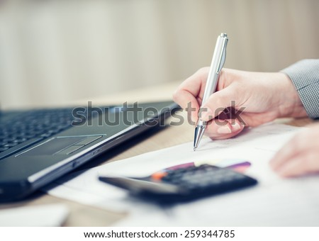 Businesswoman checking report. Toned photo, shallow depth of field. - stock photo